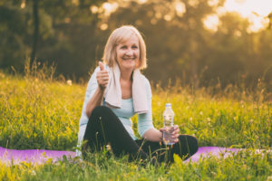 Sporty senior woman drinking water and showing thumb up